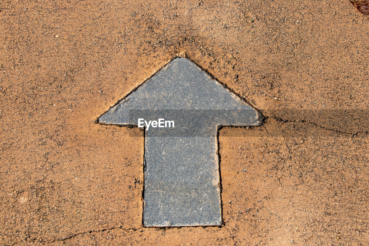 sign, shape, no people, geometric shape, arrow symbol, direction, textured, design, road, high angle view, communication, symbol, day, close-up, outdoors, transportation, footpath, guidance, stone, backgrounds, concrete