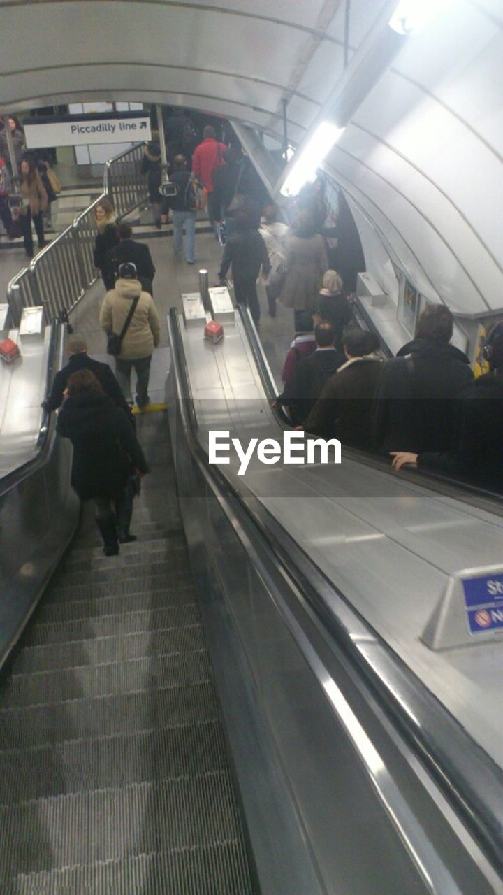 real people, large group of people, lifestyles, escalator, men, walking, women, transportation, indoors, leisure activity, public transportation, modern, travel, group of people, illuminated, motion, technology, standing, architecture, crowd, day, people, adult