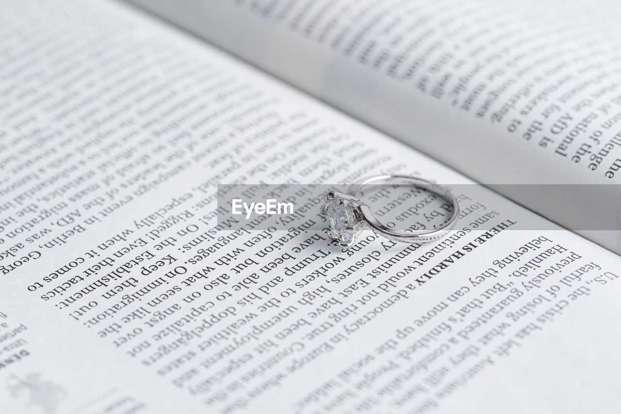 text, close-up, ring, publication, book, selective focus, paper, no people, indoors, western script, jewelry, still life, communication, wedding, full frame, celebration, wealth, event, high angle view, page