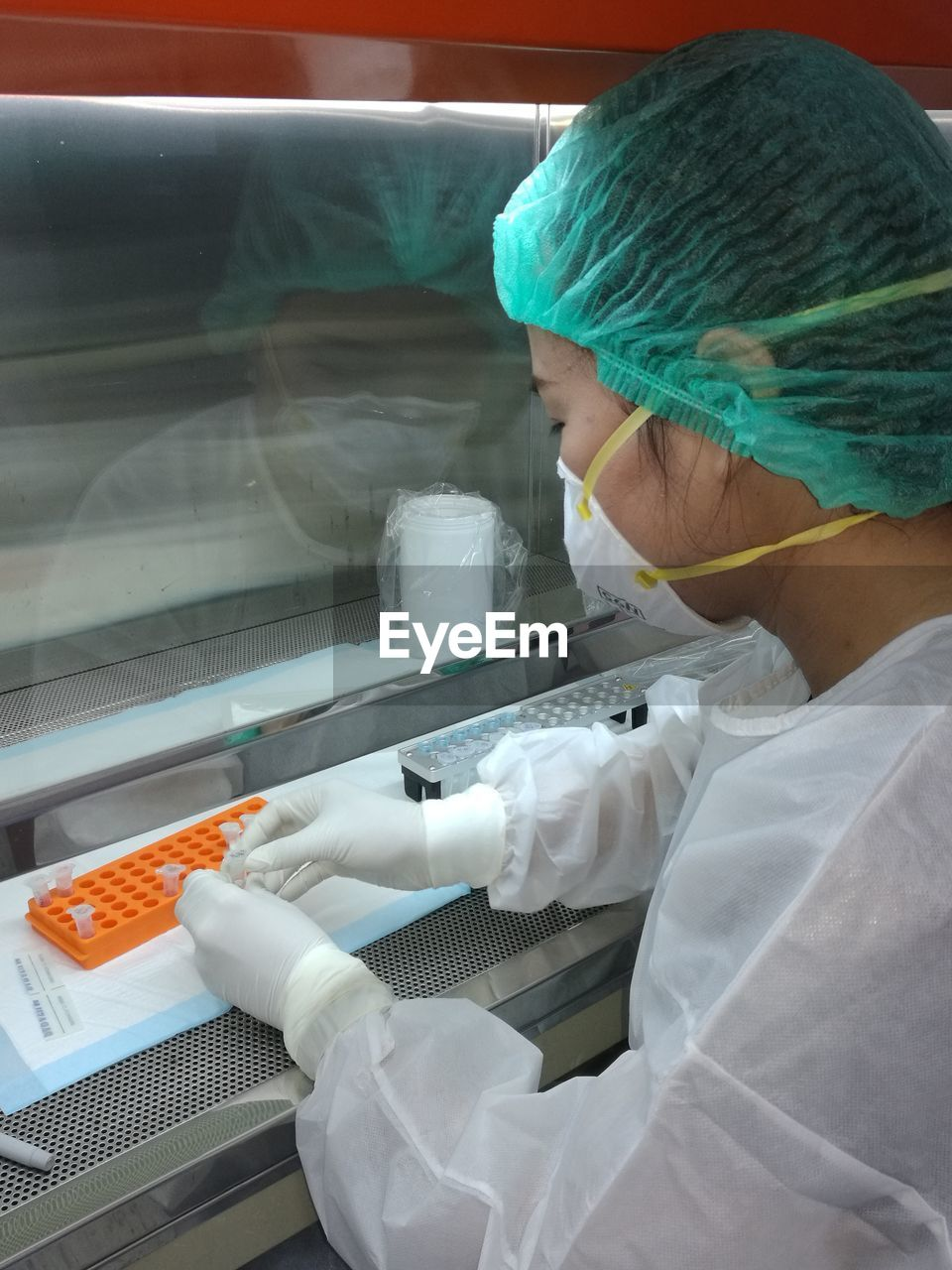 one person, occupation, healthcare and medicine, indoors, protection, adult, surgical mask, women, surgical glove, hygiene, holding, protective workwear, working, security, real people, expertise, protective glove, laboratory, research, doctor, lab coat