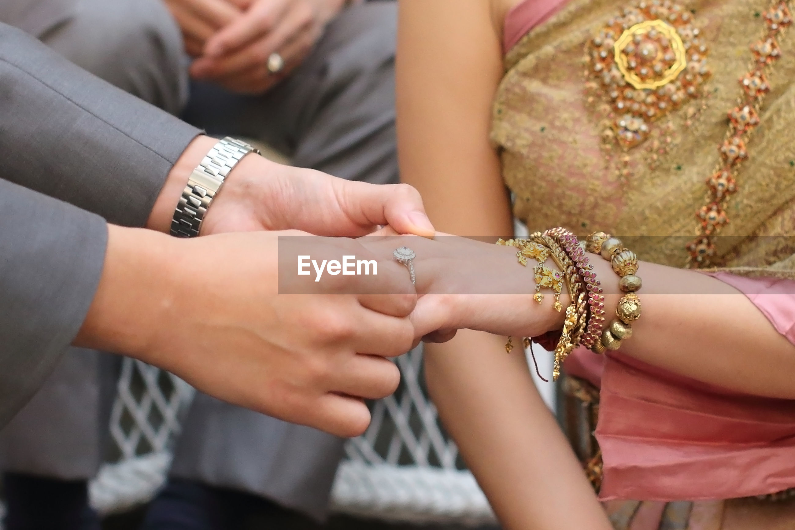 Cropped image of groom exchanging ring with bride during wedding