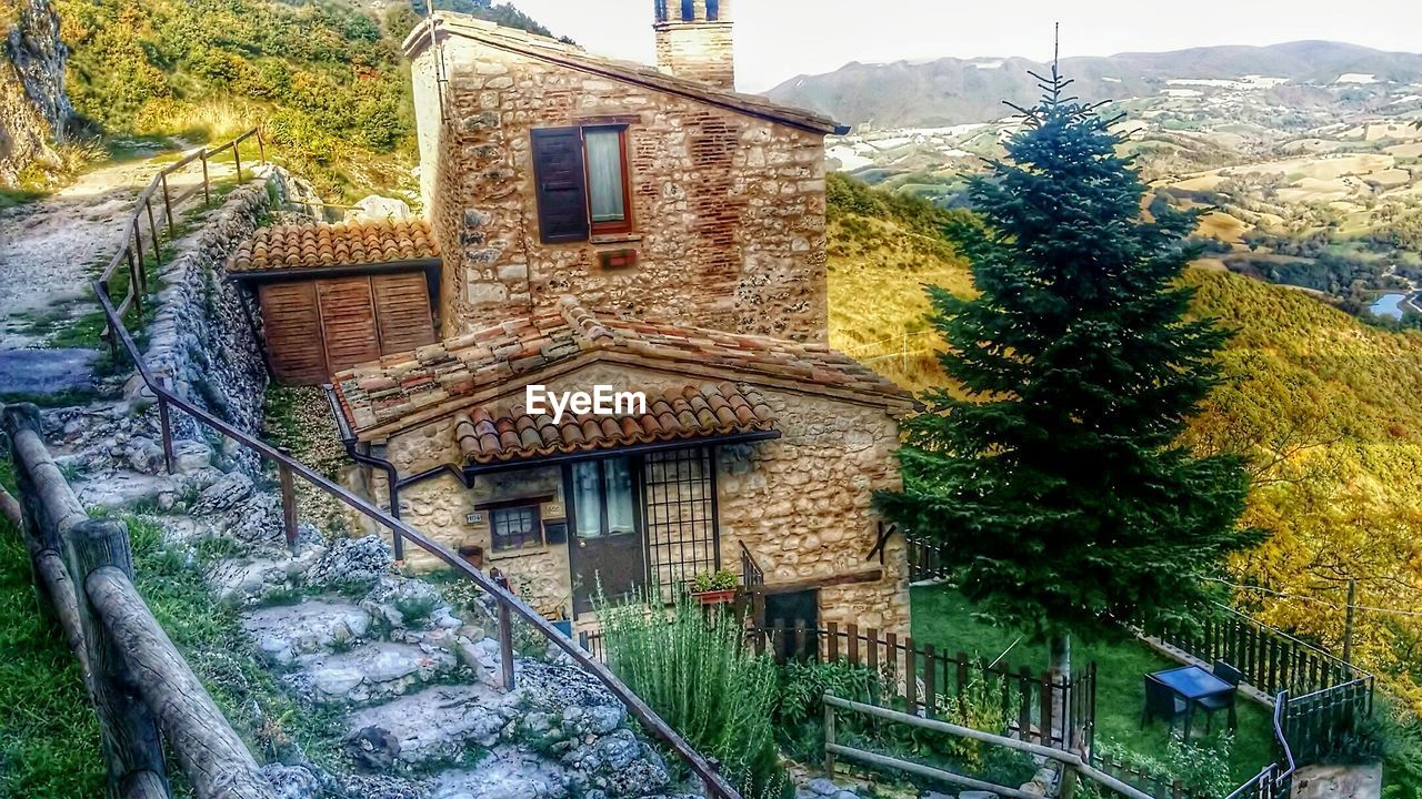building exterior, architecture, built structure, house, tree, no people, window, outdoors, day, green color, growth, nature, plant, beauty in nature, mountain, snow, sky