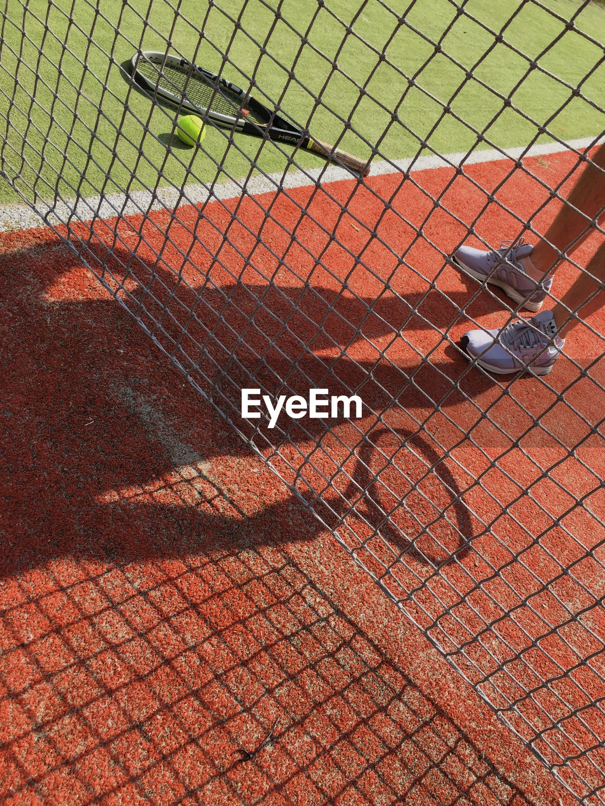 Low section of person standing by chainlink fence on tennis court