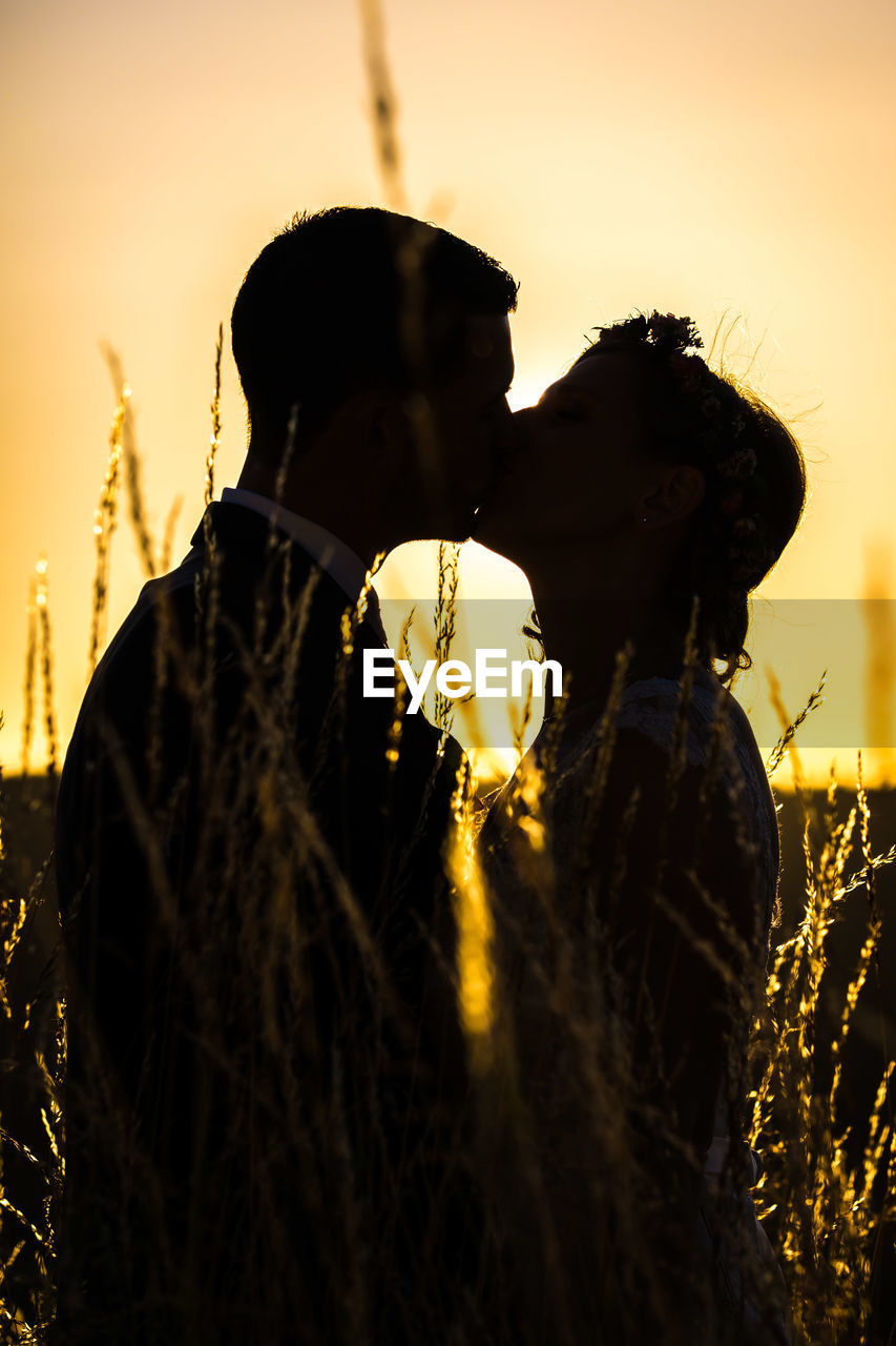 sunset, real people, field, women, silhouette, rear view, two people, outdoors, agriculture, lifestyles, sky, leisure activity, nature, rural scene, young women, men, young adult, day, people