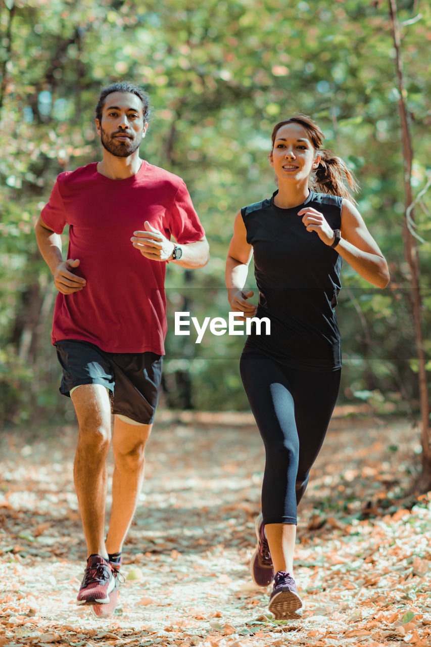 full length, lifestyles, young adult, real people, two people, people, front view, exercising, casual clothing, young men, healthy lifestyle, adult, leisure activity, portrait, focus on foreground, running, day, sports clothing, clothing, outdoors, effort