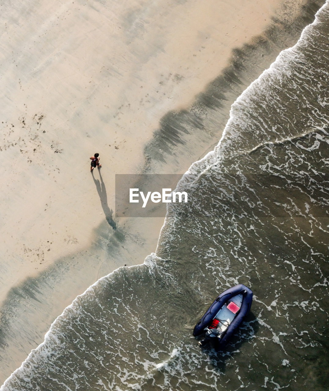 High Angle View Of Man Walking On Shore At Beach