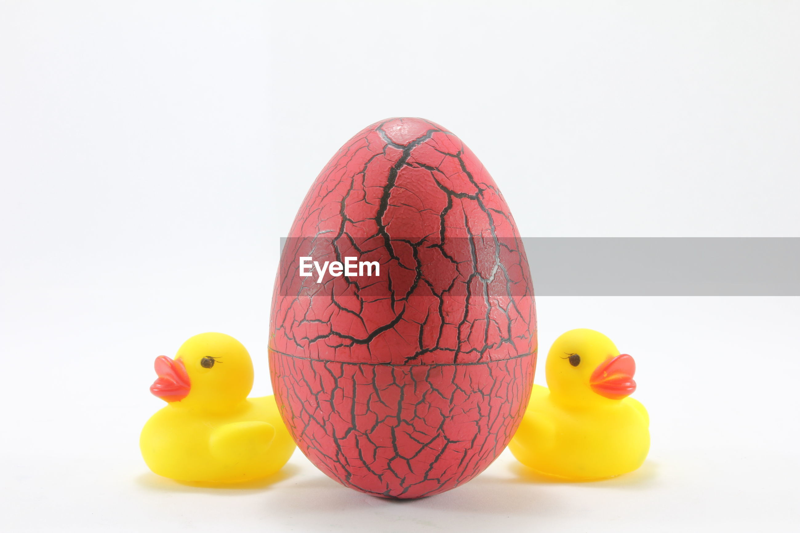 Close-up of easter egg amidst yellow rubber ducks over white background