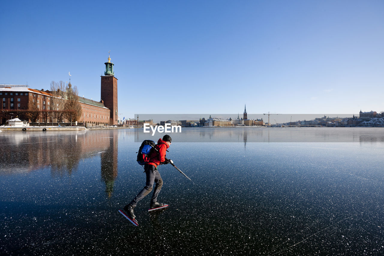 MAN STANDING ON WATER AGAINST CLEAR SKY