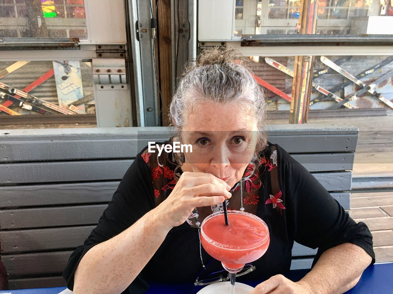 Portrait of mature woman drinking cocktail while sitting at restaurant