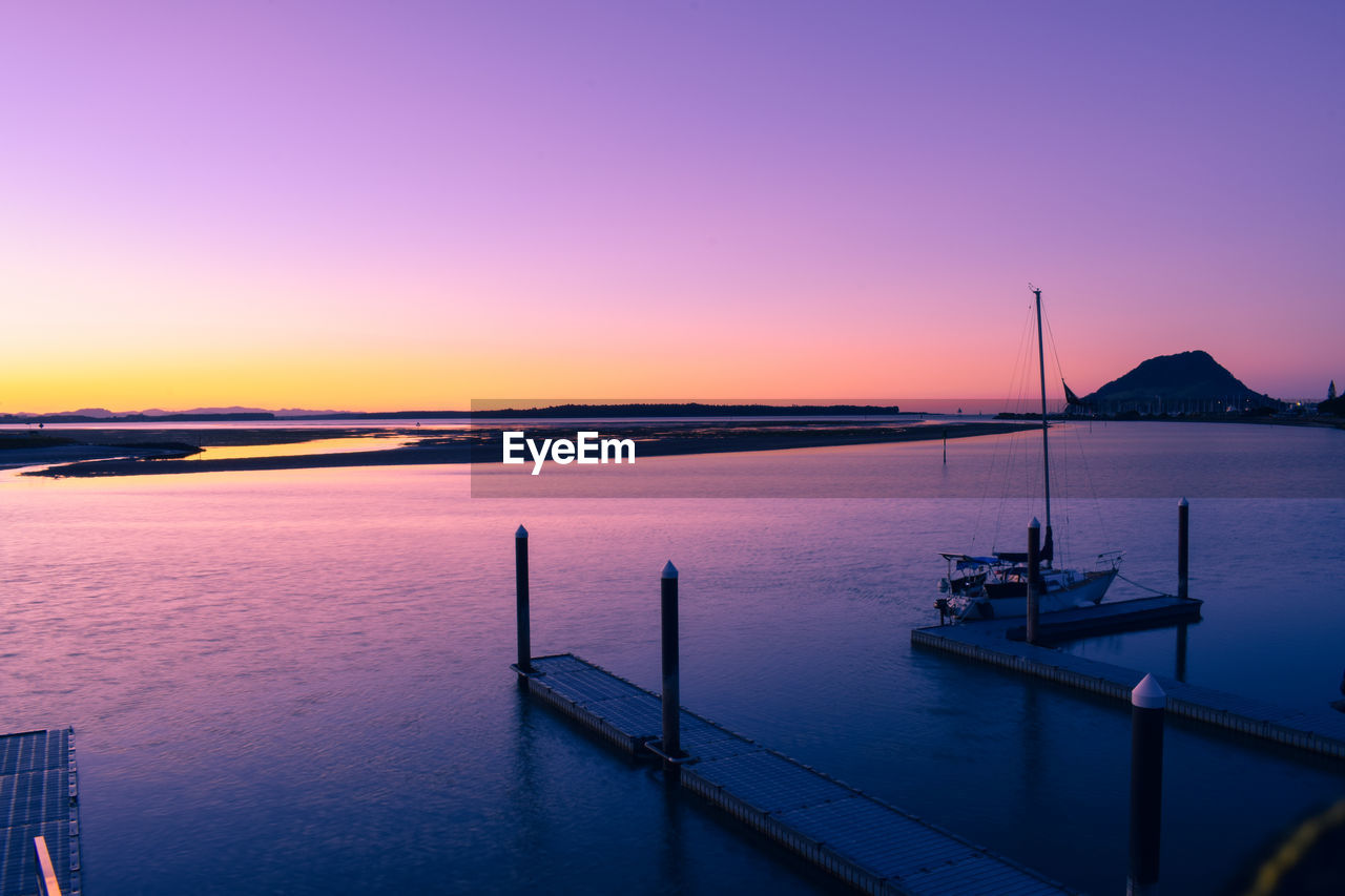 sunset, sky, water, beauty in nature, scenics - nature, sea, orange color, tranquility, tranquil scene, nature, nautical vessel, idyllic, transportation, no people, pier, copy space, outdoors, non-urban scene, travel, purple