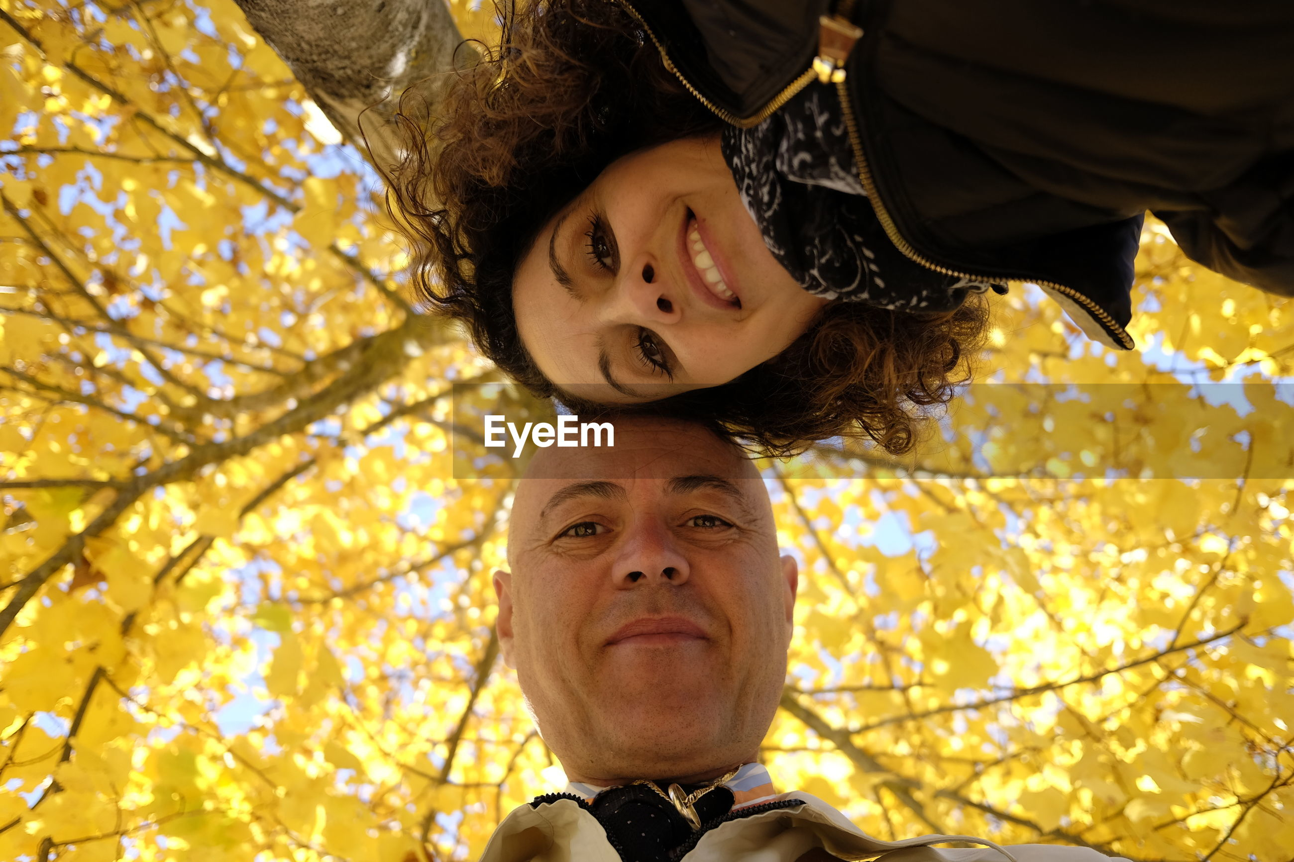Low angle portrait of family standing against trees during autumn