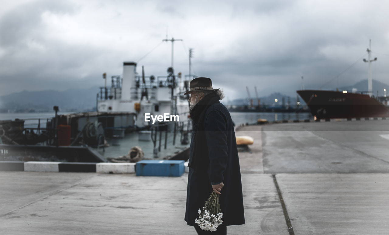 Man Standing At Harbor Against Sky