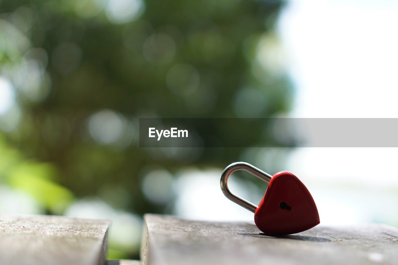 red, close-up, focus on foreground, selective focus, no people, day, still life, outdoors, heart shape, table, positive emotion, nature, solid, love, green color, single object, metal, wood - material, white color, copy space, personal accessory