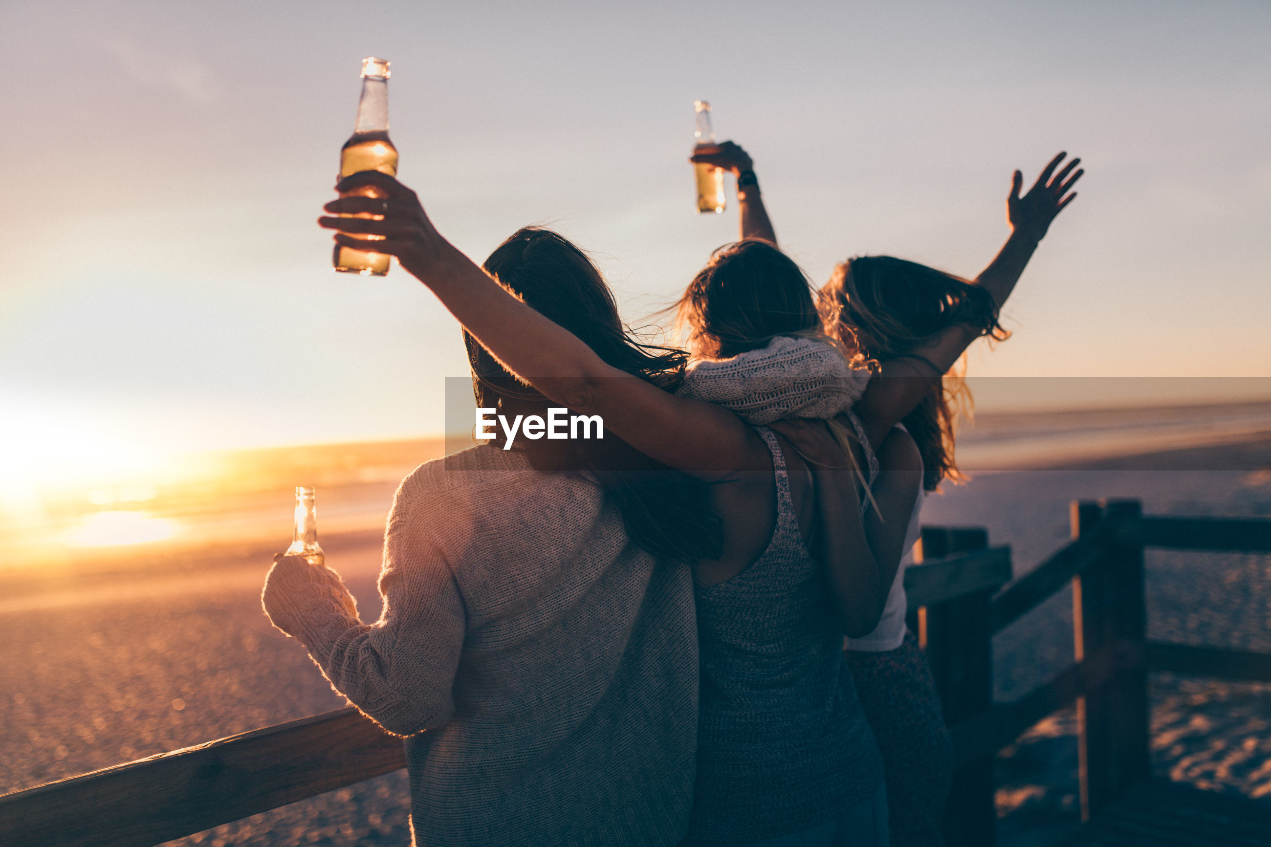 Women holding beer bottles while standing by railing against sea during sunset