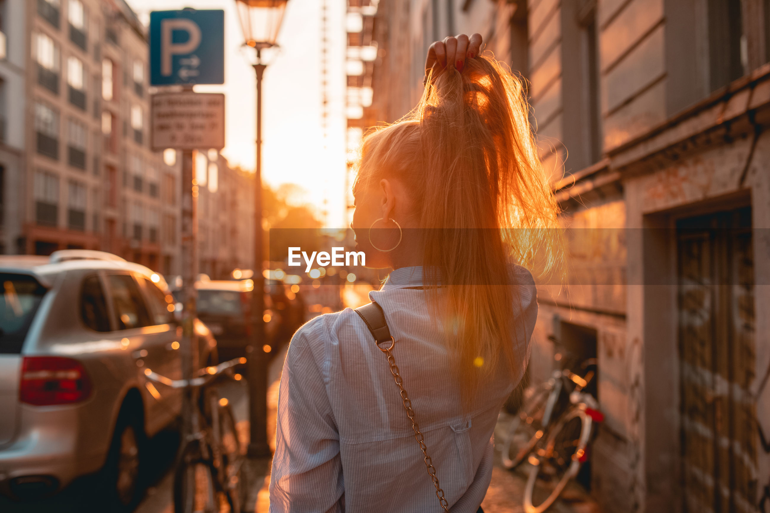 Rear view of young woman with hand in hair while standing on sidewalk during sunset