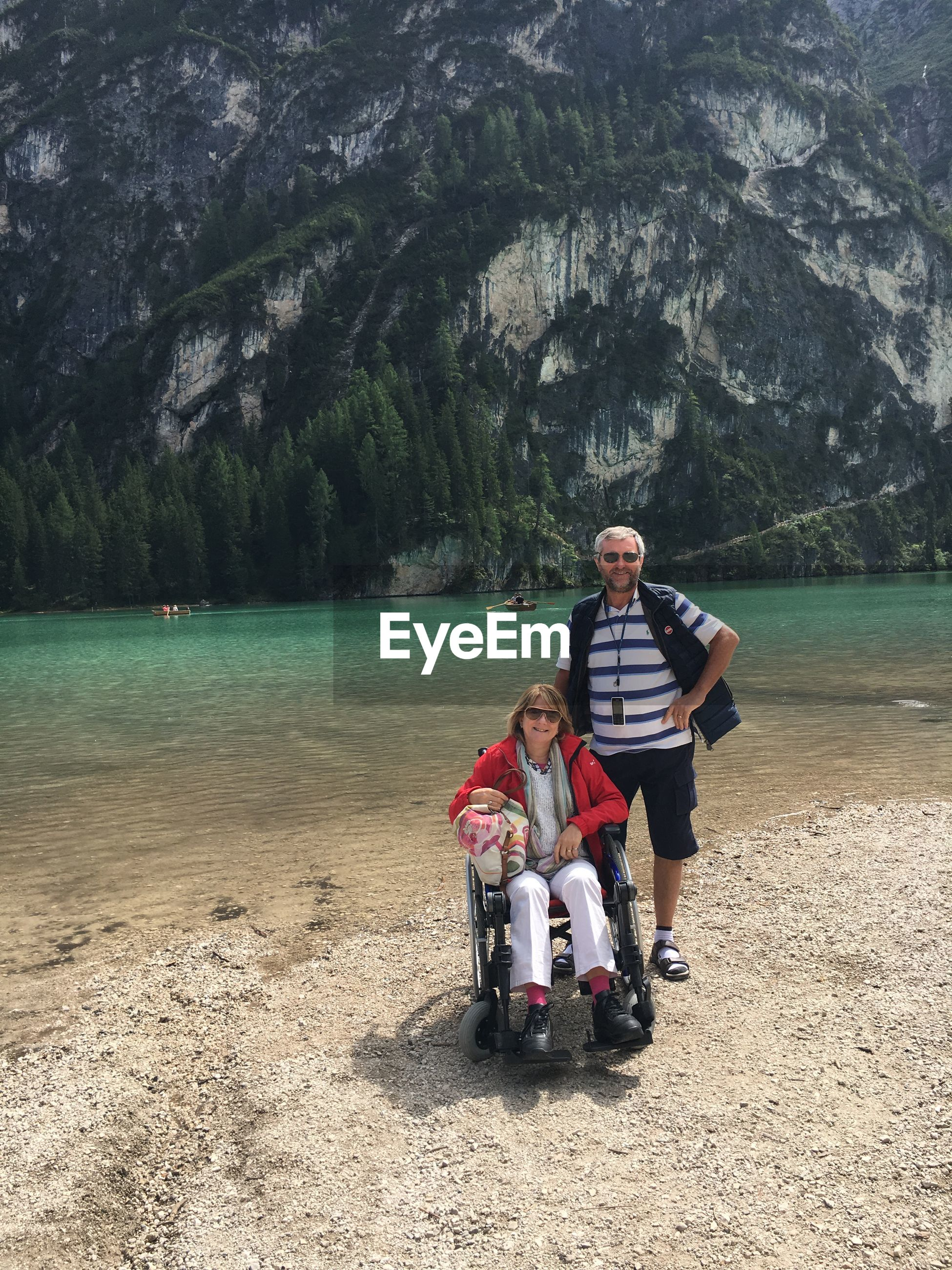 Portrait of smiling man with woman sitting on wheelchair against lake