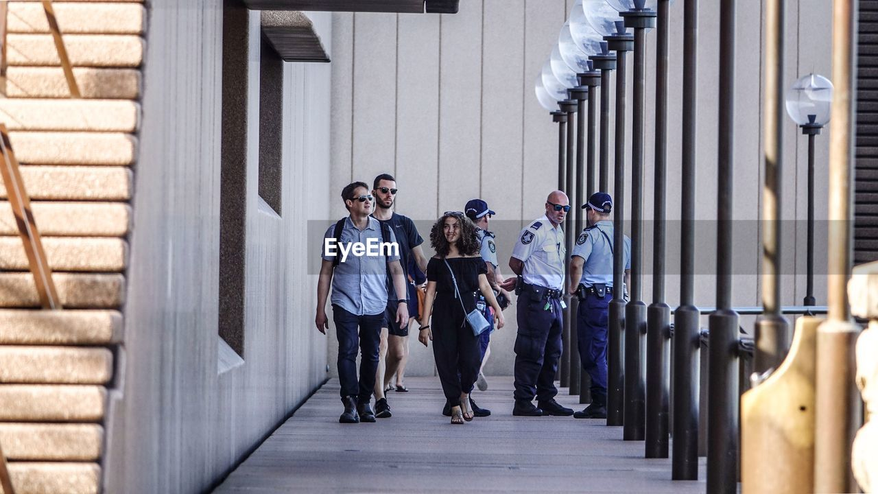 FULL LENGTH OF PEOPLE WALKING ON BUILDING