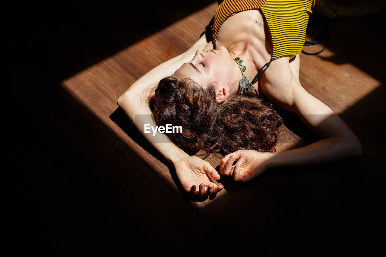 High angle view of mid adult woman sleeping on hardwood floor at home