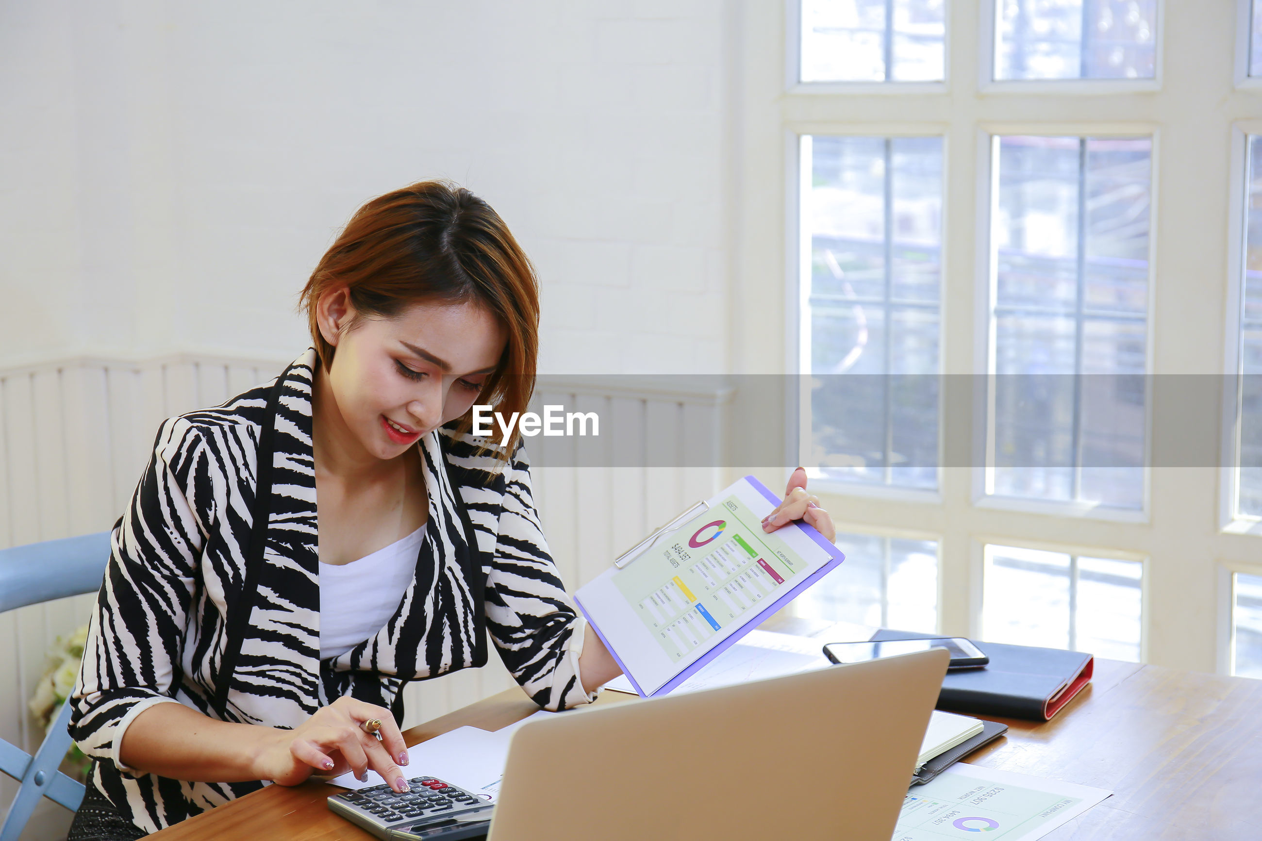 Young businesswoman using calculator while analyzing document at desk in office
