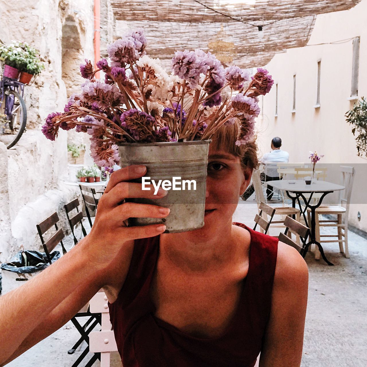 Portrait Of Woman Holding Flower Pot In Cafe