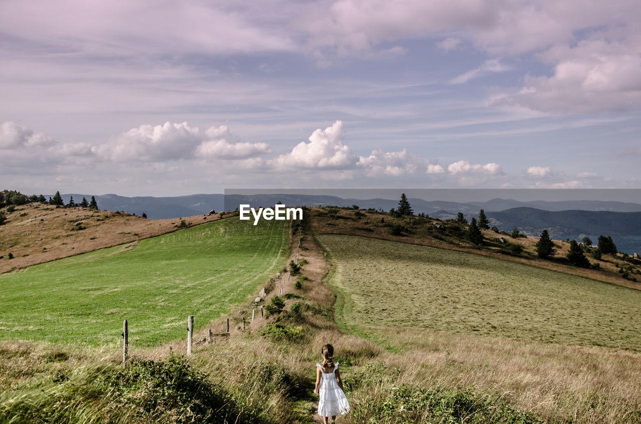 Rear View Of Girl Walking On Grassy Mountain