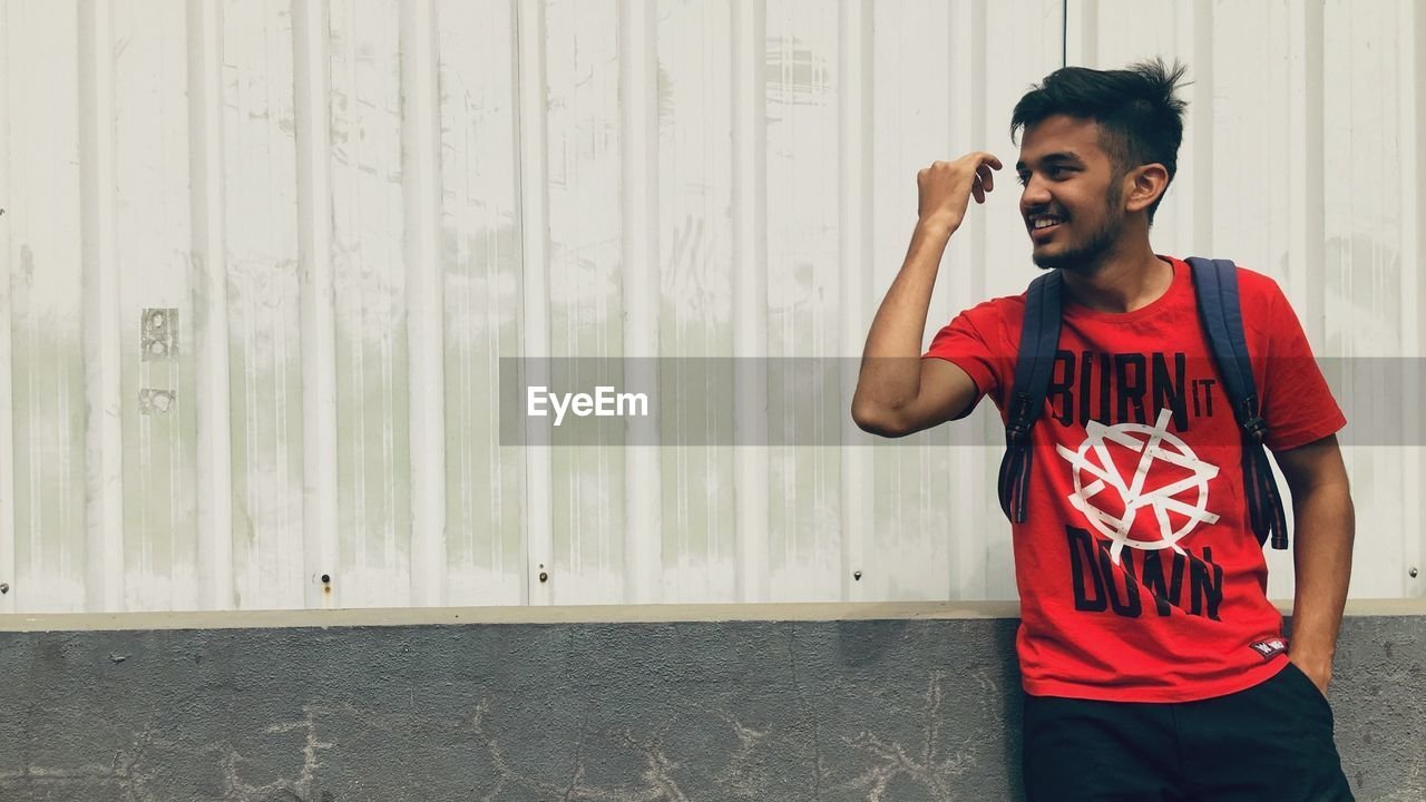 Smiling young man looking away while standing against wall