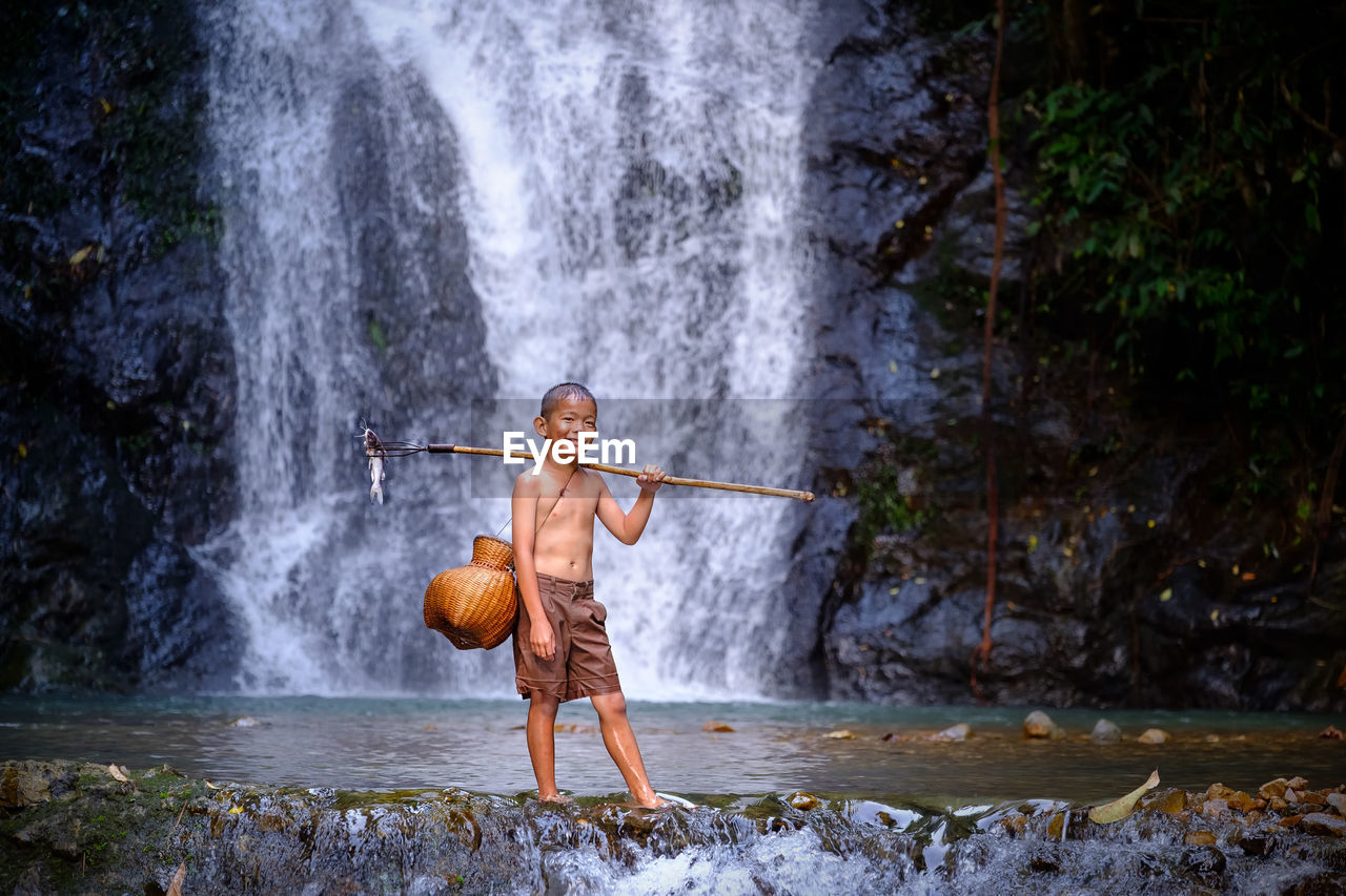 Full Length Of Shirtless Boy Standing In River Against Waterfall