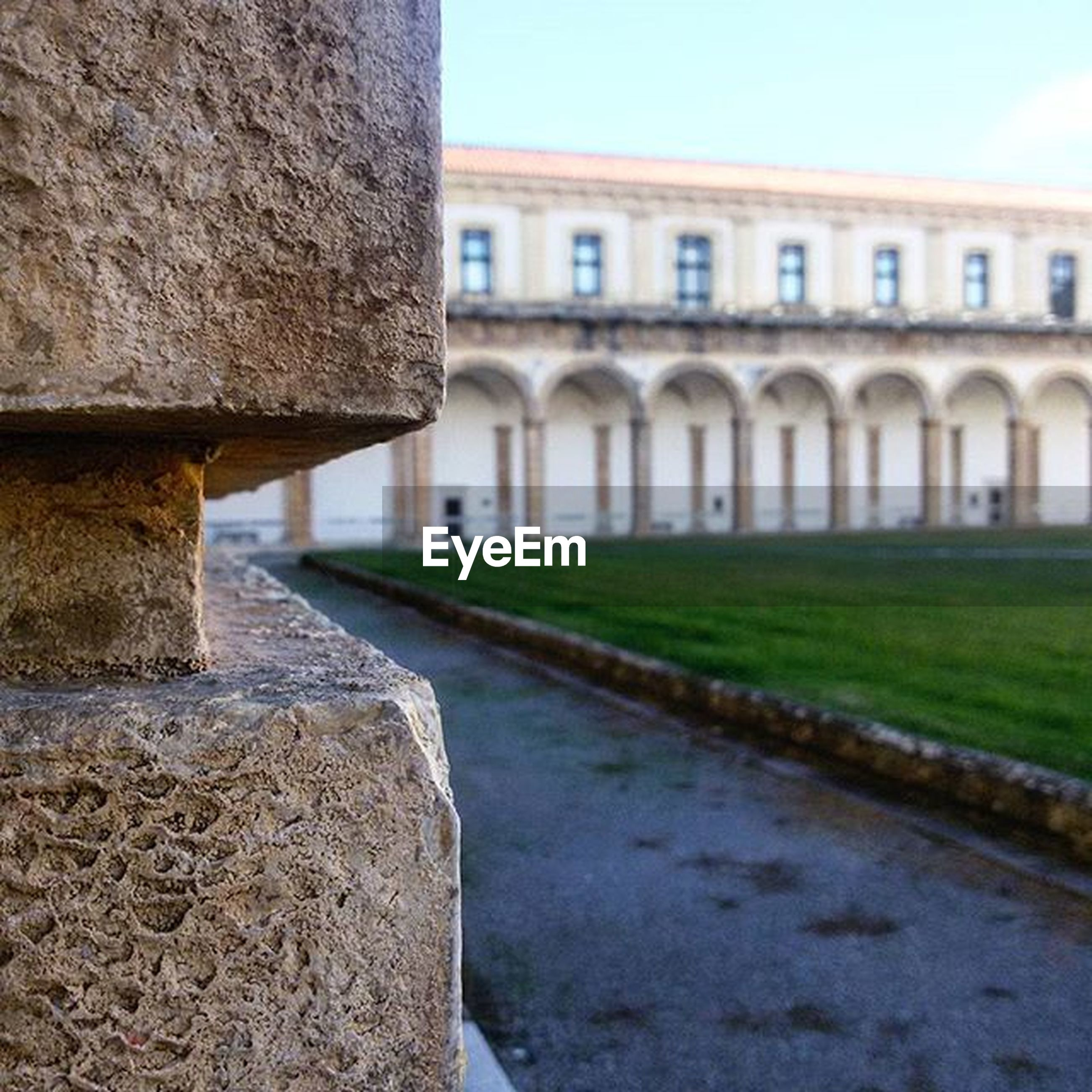 architecture, built structure, building exterior, grass, water, in a row, sky, day, history, outdoors, stone material, architectural column, surface level, no people, green color, the past, sunlight, building, clear sky, incidental people