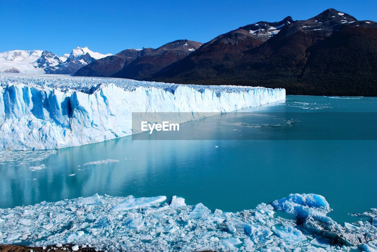 Glaciers Melting In River Against Mountains During Winter