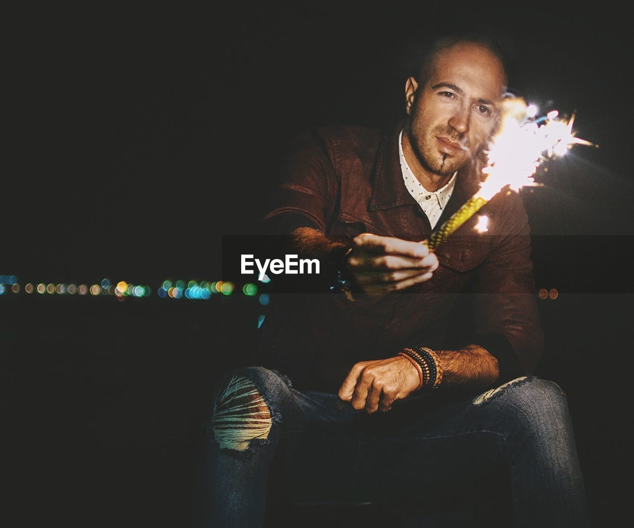 Man Holding Illuminated Cracker At Night
