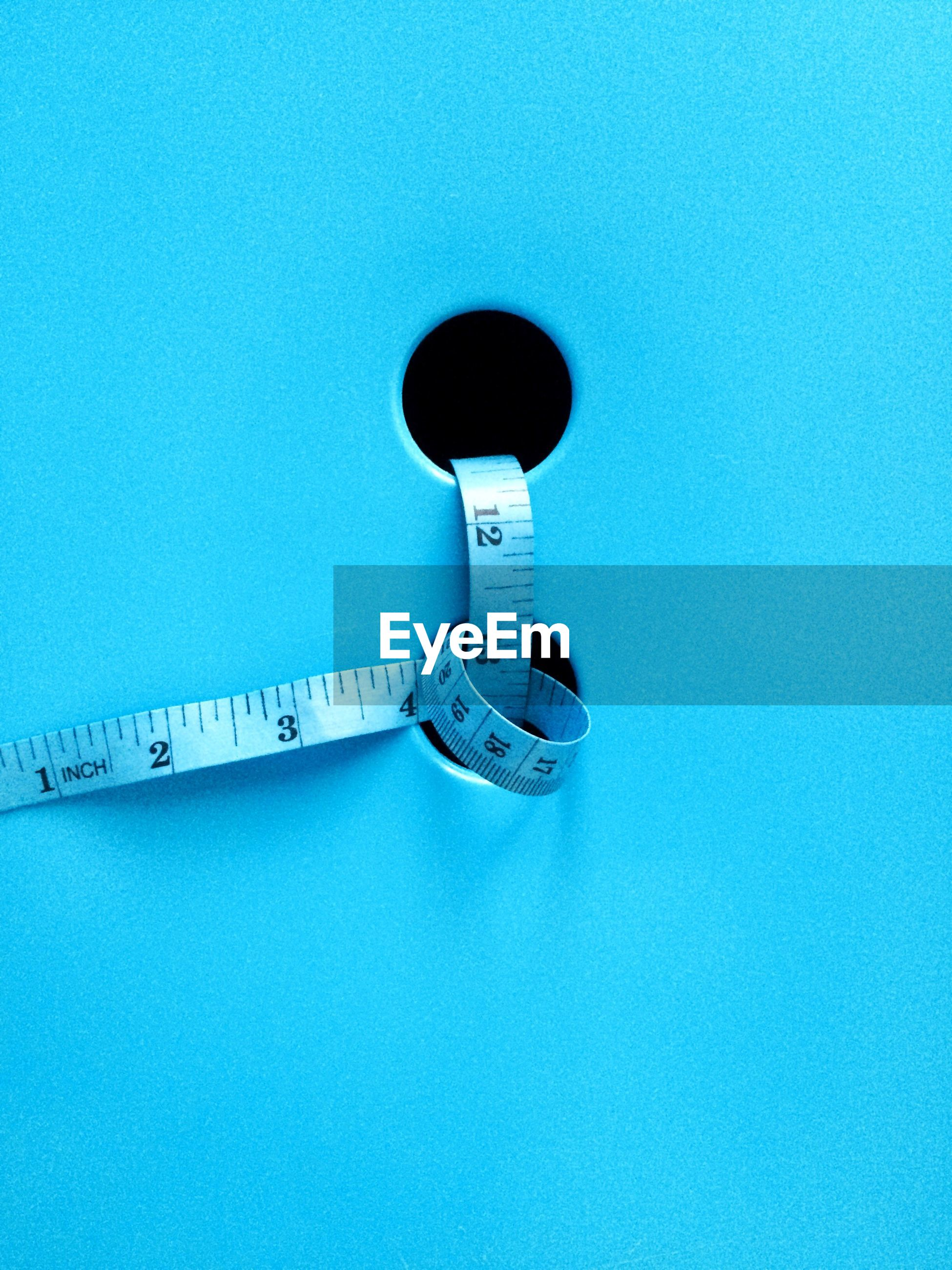 Close-up of measuring tape on blue table