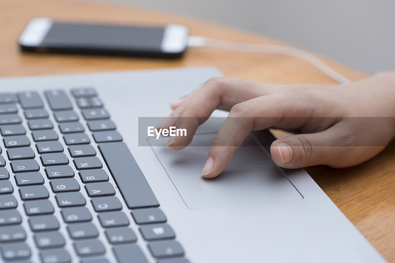 human hand, hand, keyboard, computer equipment, computer, human body part, computer keyboard, technology, communication, real people, wireless technology, one person, indoors, selective focus, connection, human finger, laptop, body part, unrecognizable person, finger, typing, using laptop, surfing the net, computer key