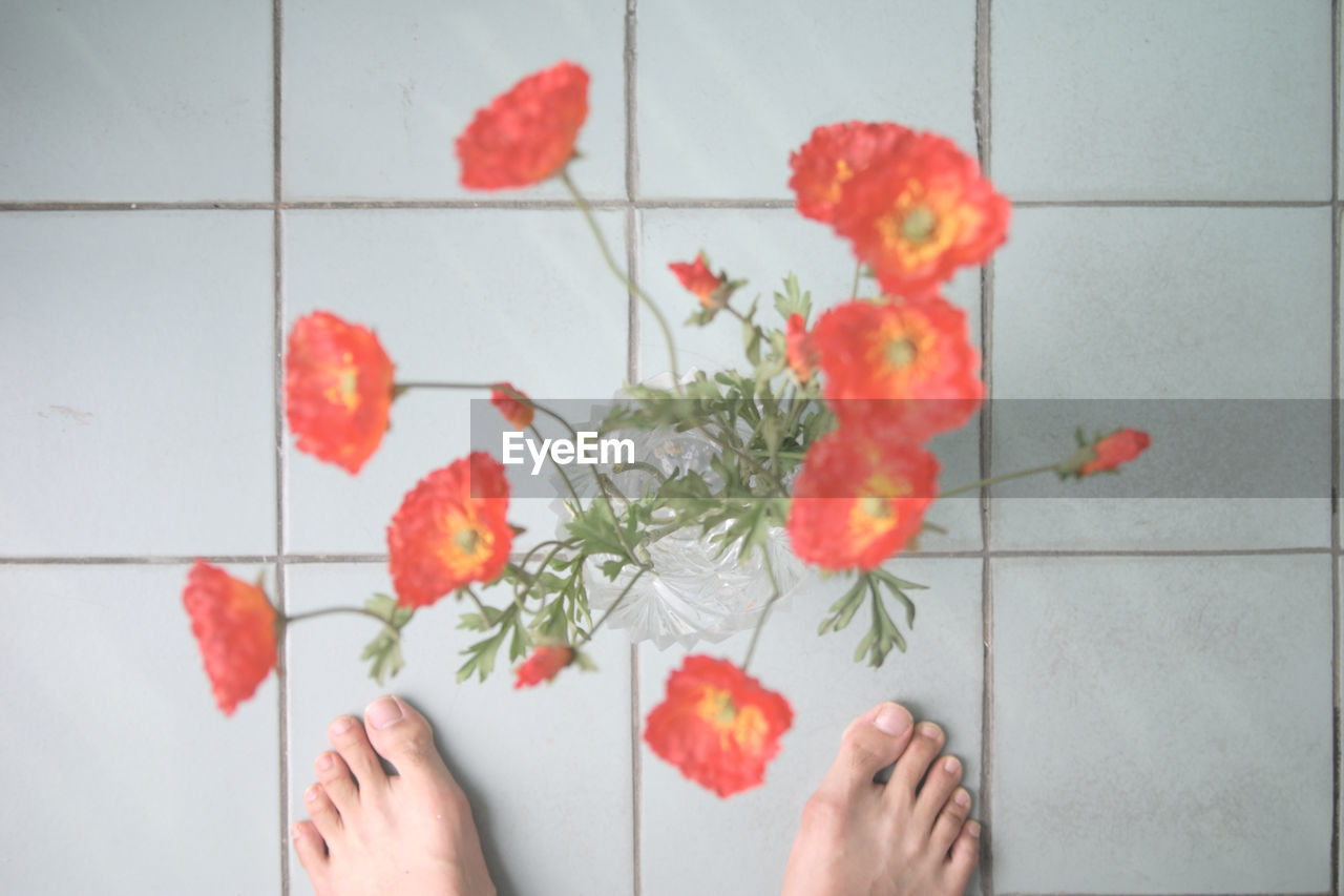 Low Section Of Person Standing By Flower Vase On Tiled Floor At Home