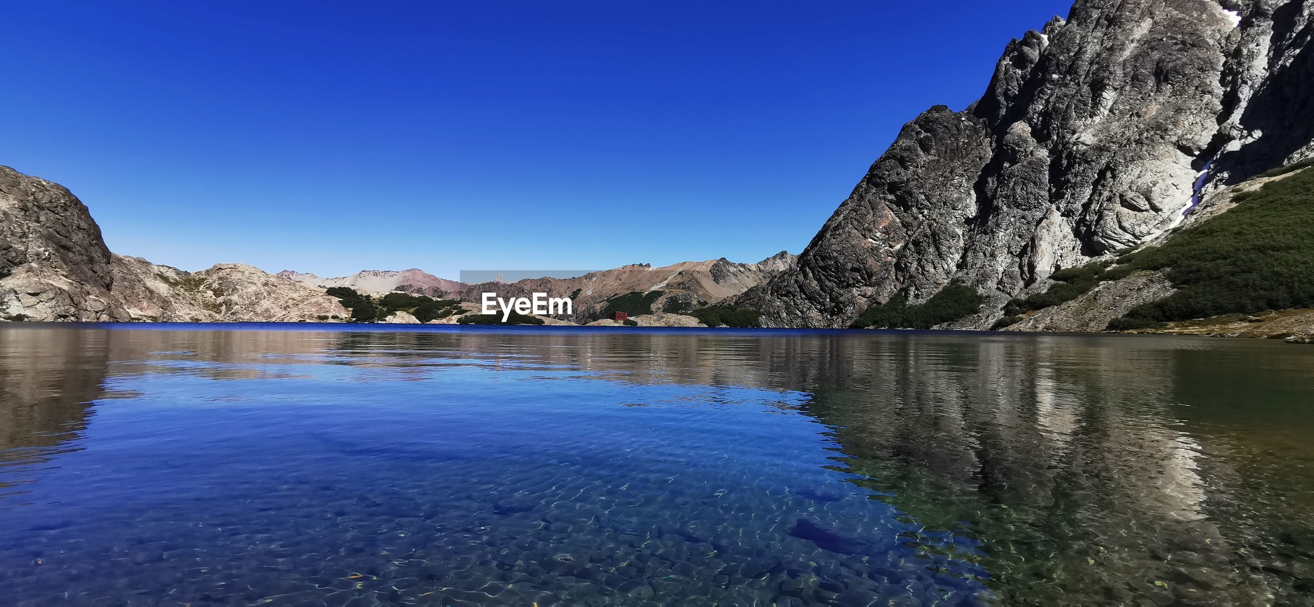 SCENIC VIEW OF LAKE AND ROCK FORMATION AGAINST CLEAR BLUE SKY