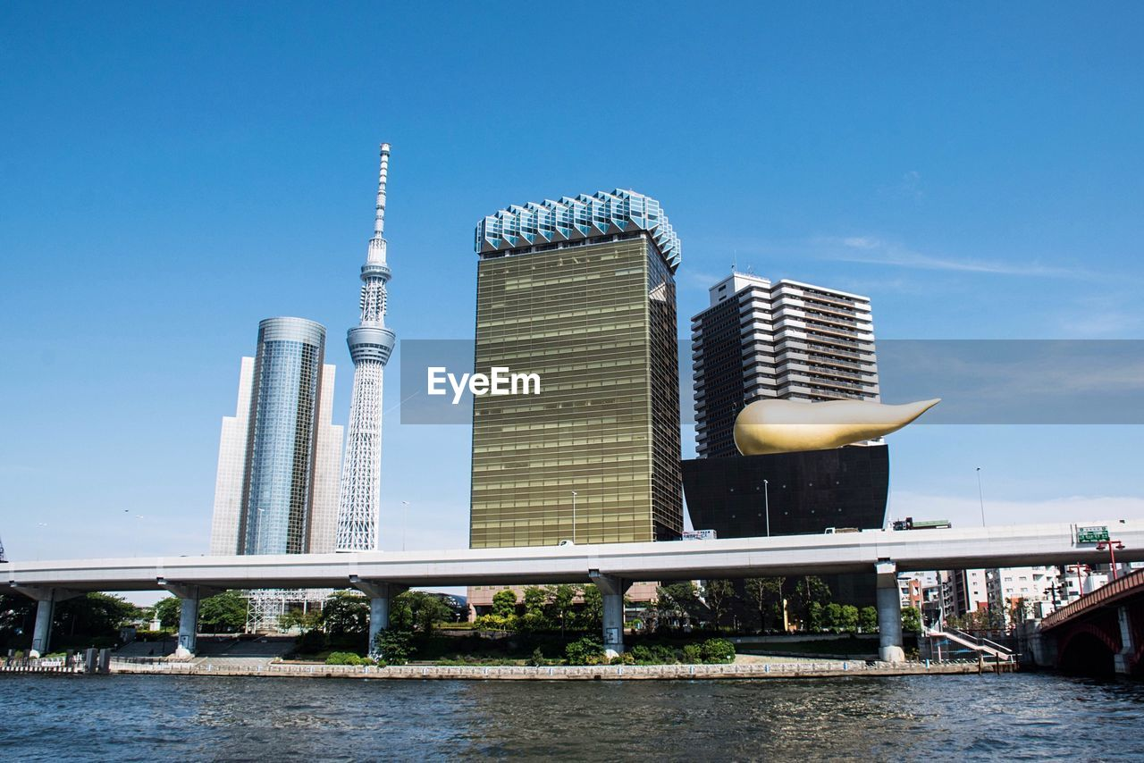 architecture, built structure, building exterior, tower, city, skyscraper, sky, modern, river, outdoors, day, blue, no people, clear sky, water, urban skyline
