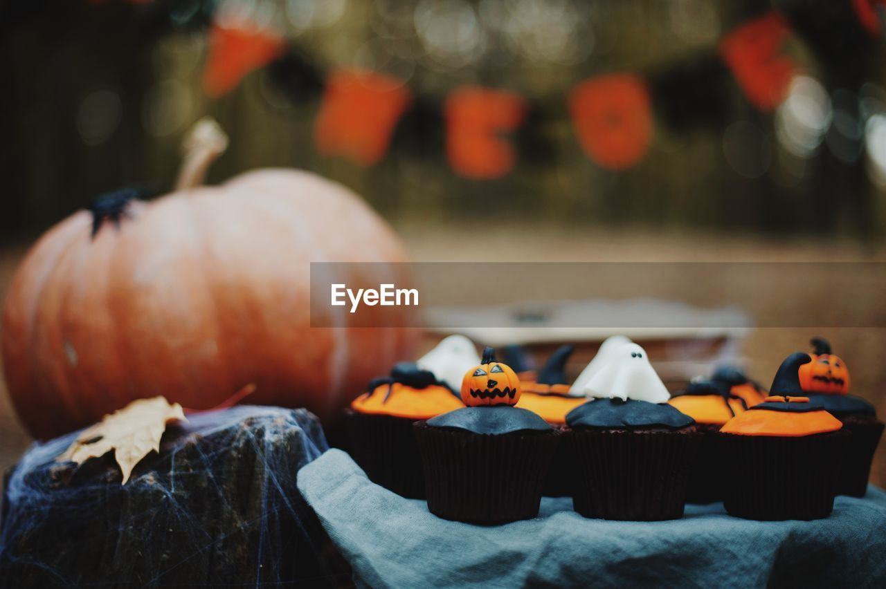 Close-Up Of Cupcakes And Pumpkin During Halloween Celebration