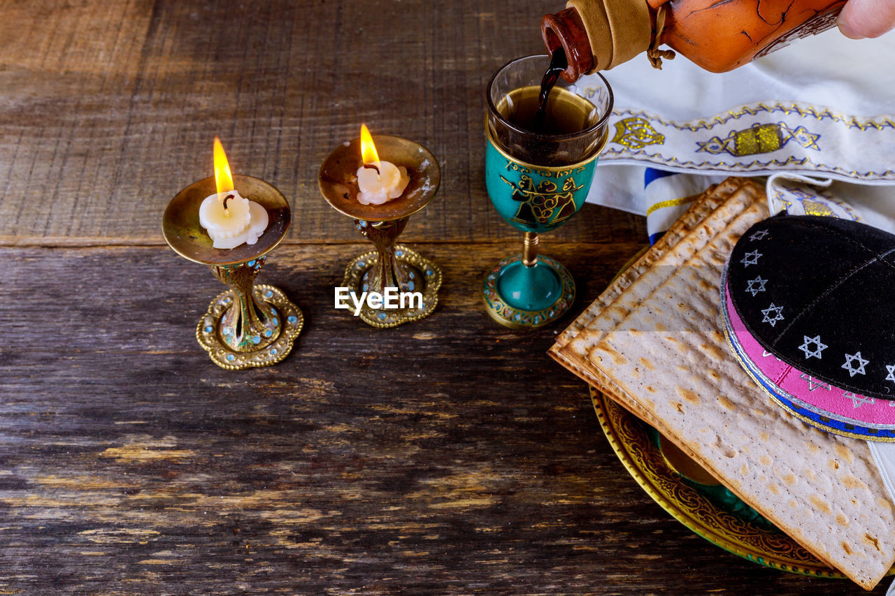 table, candle, high angle view, food and drink, indoors, food, flame, burning, fire, plate, wood - material, freshness, close-up, no people, glass, celebration, drink, religion, fire - natural phenomenon, tea light