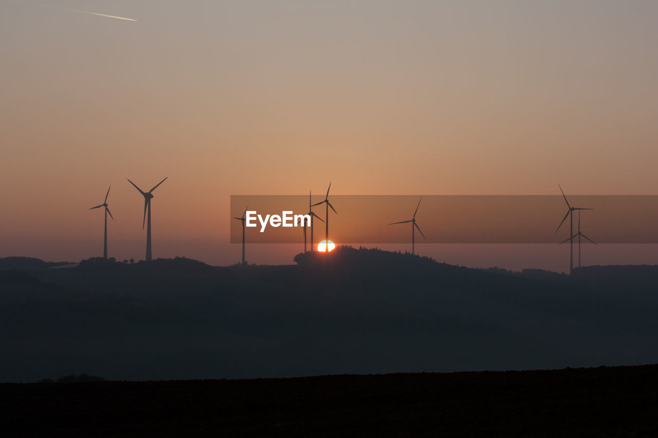 sunset, fuel and power generation, wind turbine, wind power, environment, renewable energy, environmental conservation, alternative energy, sky, turbine, silhouette, beauty in nature, landscape, scenics - nature, land, field, nature, orange color, technology, non-urban scene, no people, sustainable resources