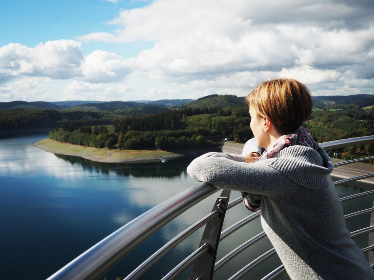 railing, real people, one person, cloud - sky, sky, leisure activity, lifestyles, nature, water, day, mountain, casual clothing, beauty in nature, river, looking at view, architecture, scenics - nature, outdoors, hairstyle