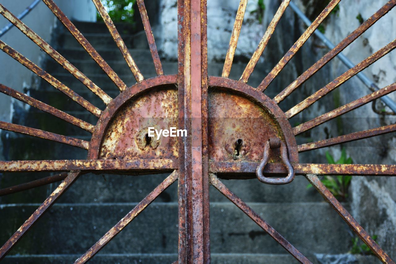 Close-Up Of Closed Rusty Metal Gate By Steps