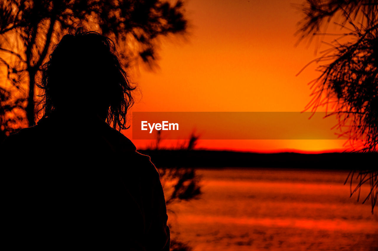 sunset, orange color, sky, silhouette, beauty in nature, one person, scenics - nature, nature, real people, rear view, land, tree, lifestyles, leisure activity, tranquility, tranquil scene, plant, headshot, idyllic, outdoors, hairstyle