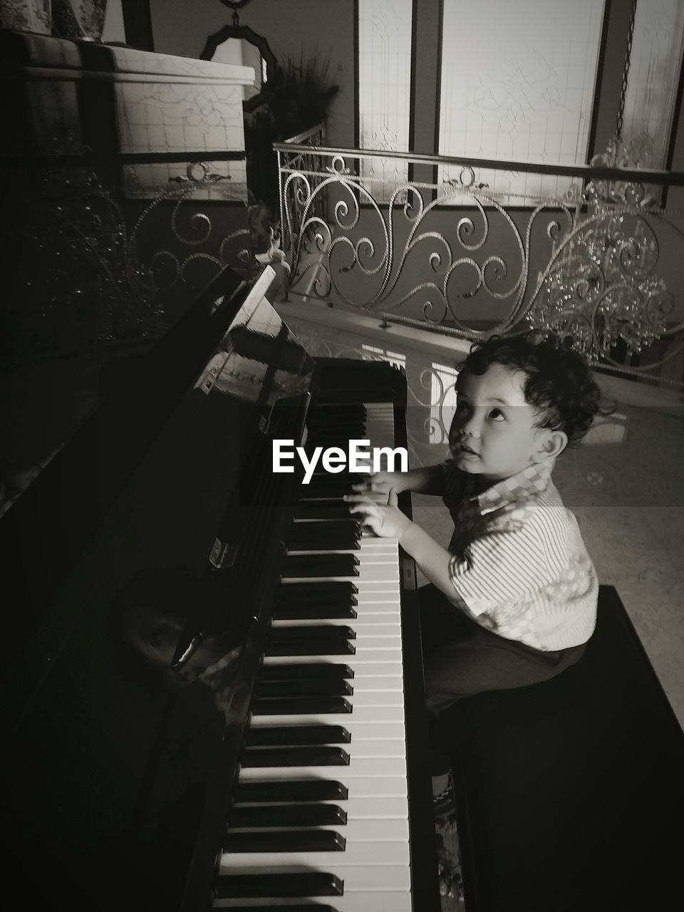 High angle view of cute boy playing piano at home