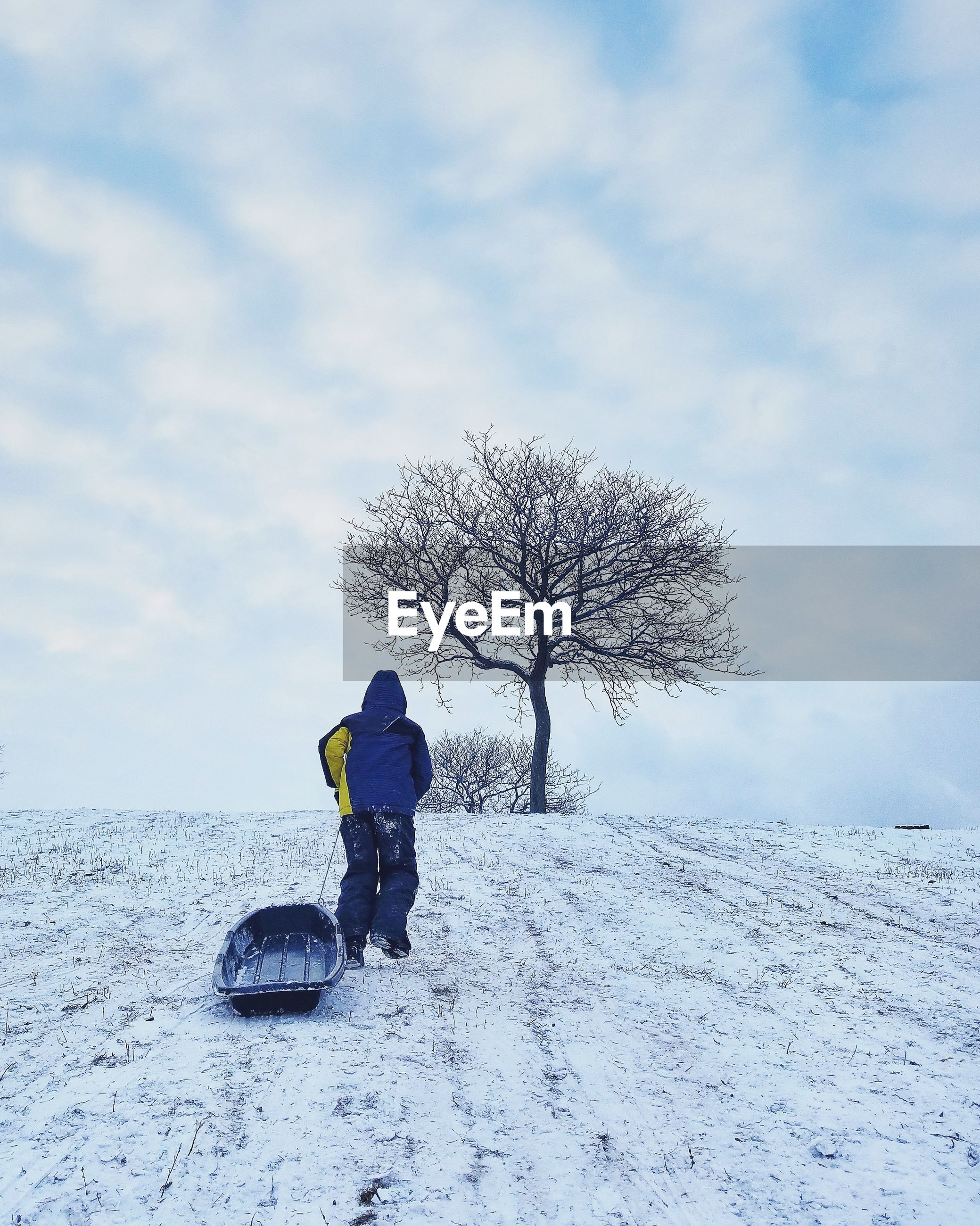Man with sled walking on snow covered field against sky during winter