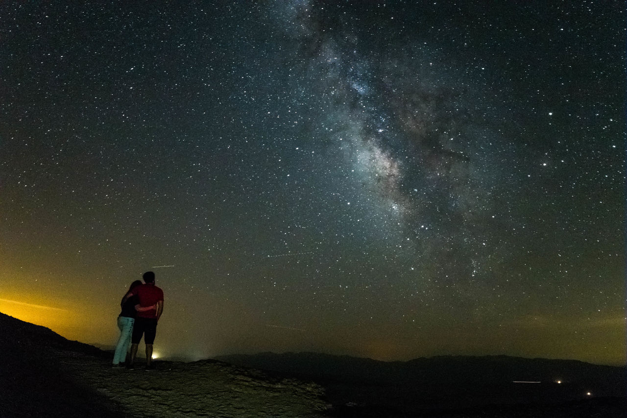 Couple Embracing At Desert Against Star Field