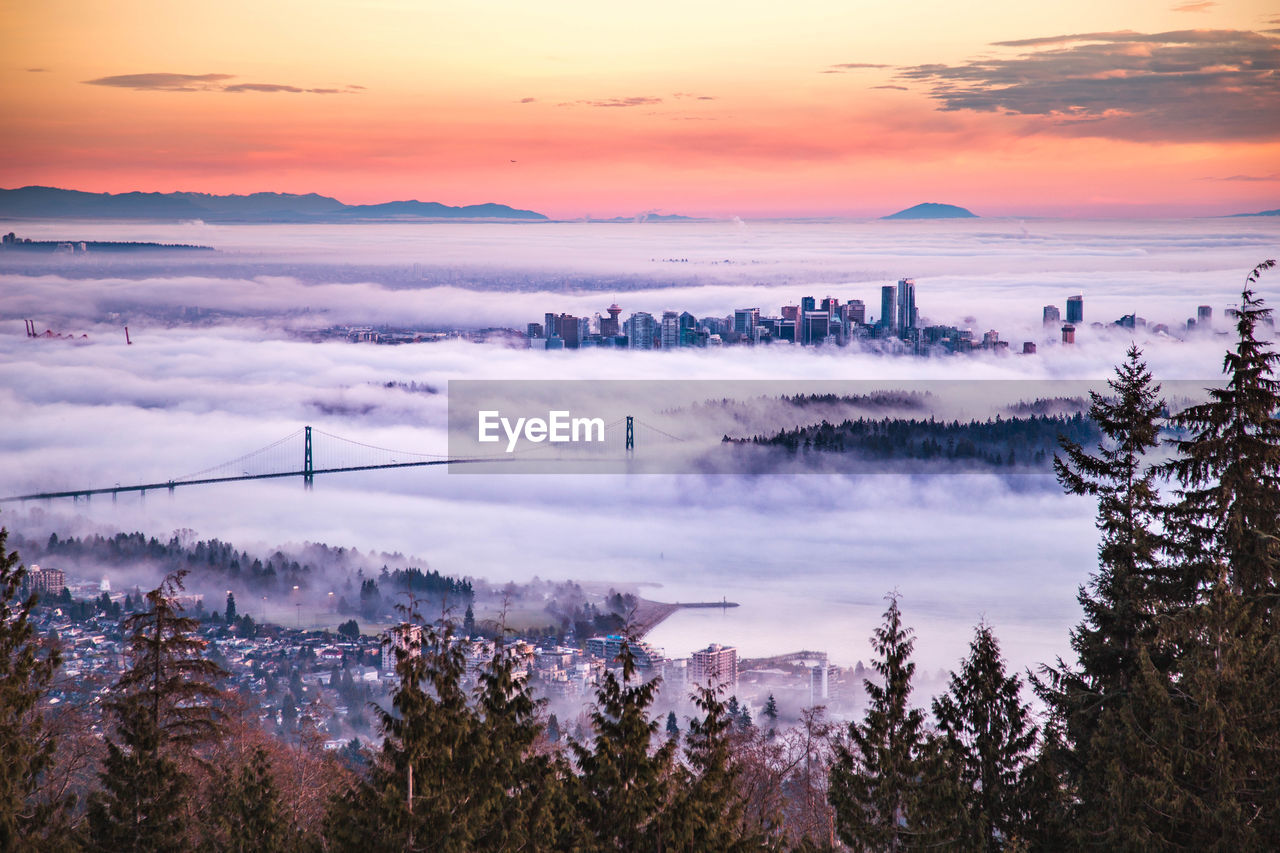 Aerial View Cityscape During Foggy Weather Against Sky During Sunset