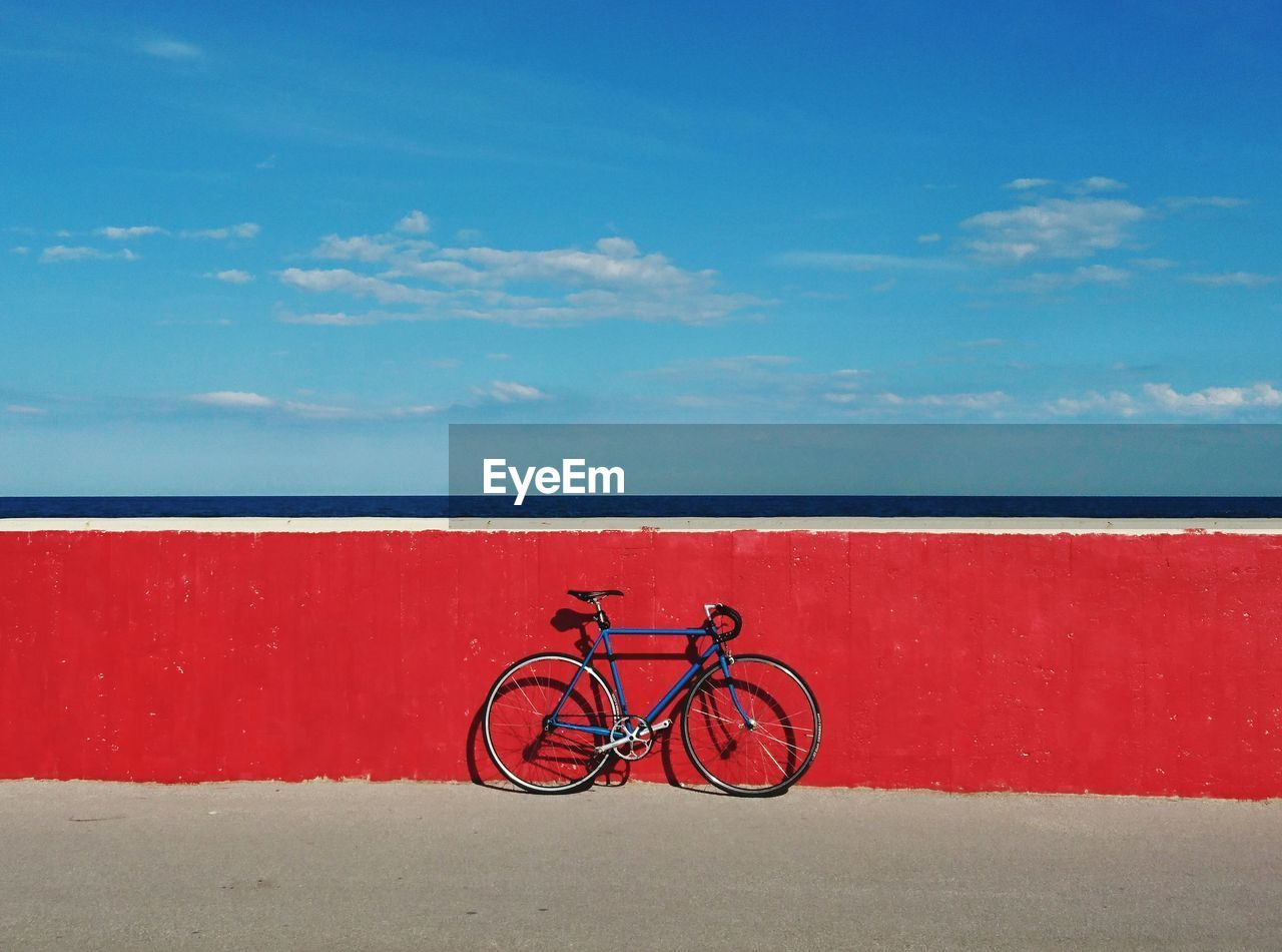 Bicycle against red wall