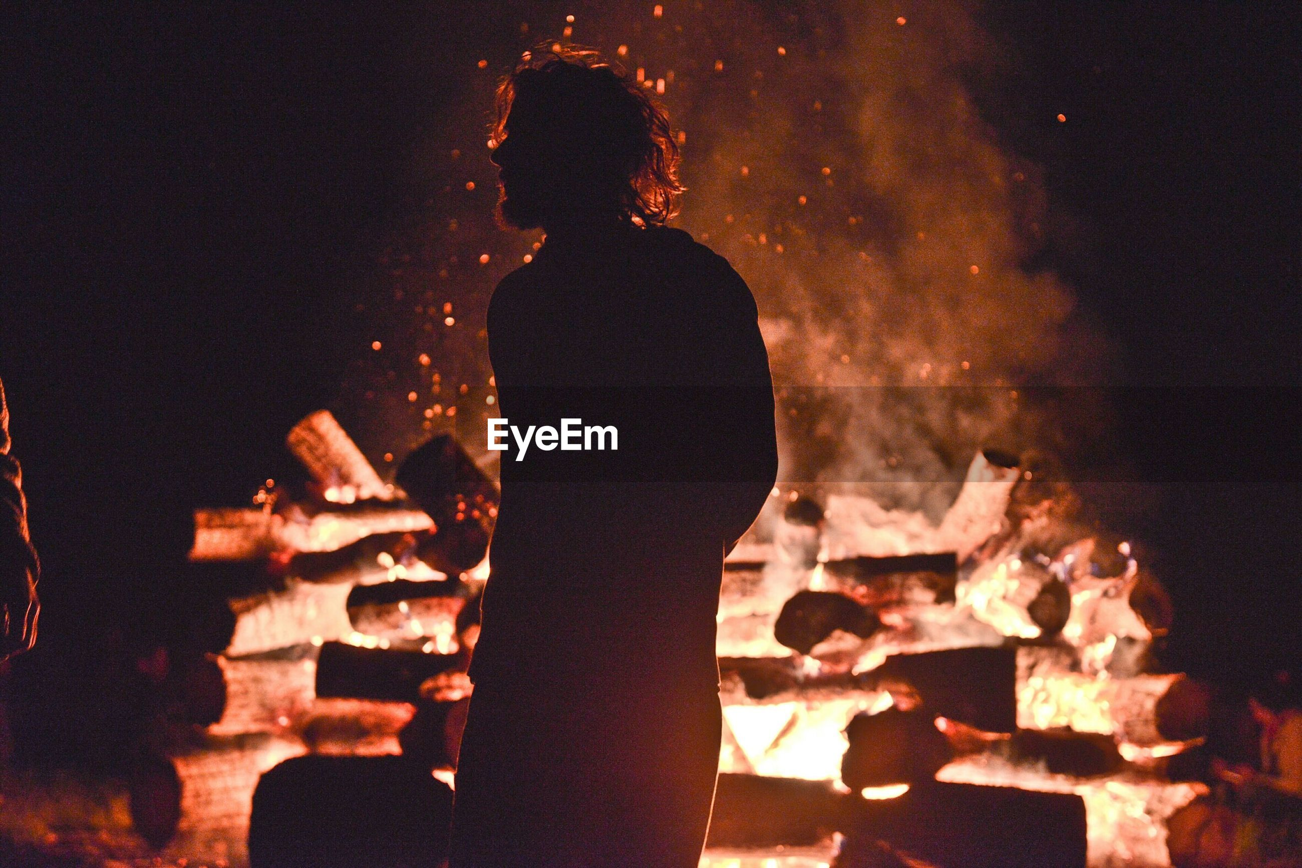 Man standing by bonfire on field at night