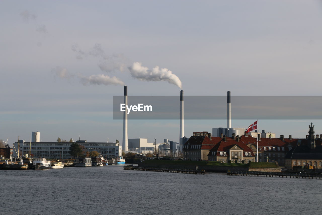 Smoke Emitting From Factory By River Against Sky