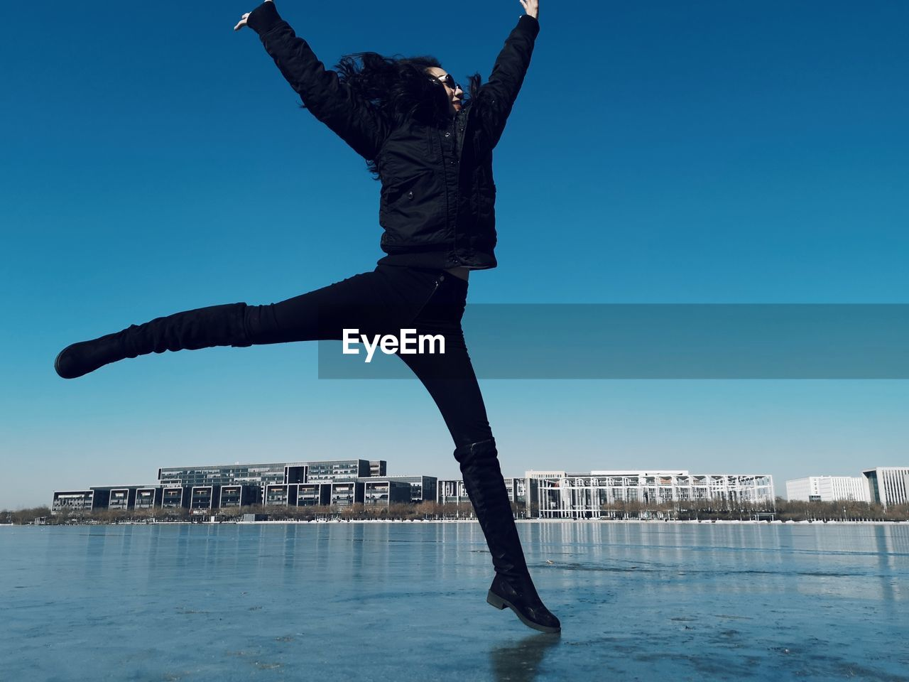 Woman jumping on frozen lake against clear blue sky