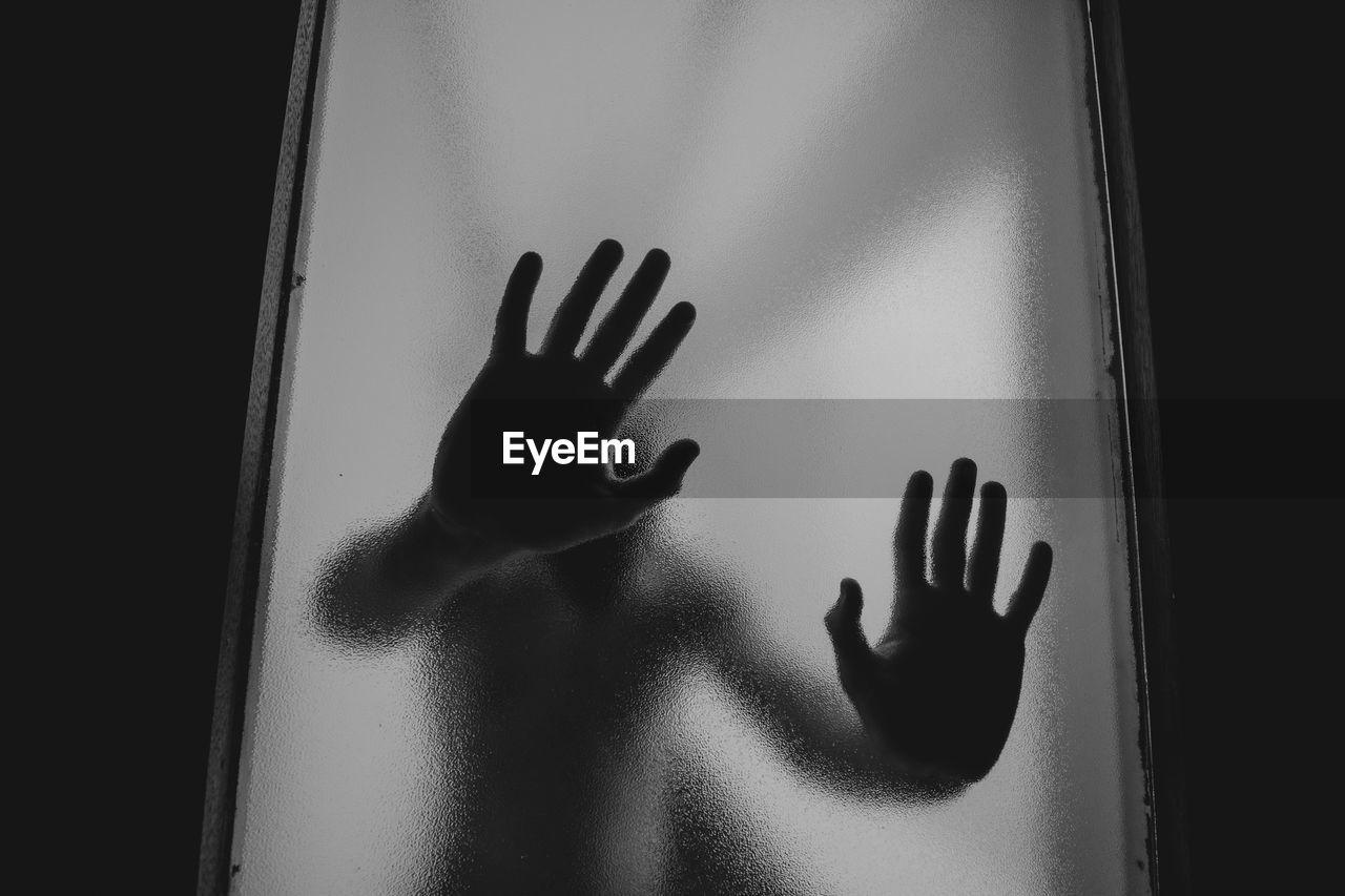 Shadow Of Woman Hand On Glass Window